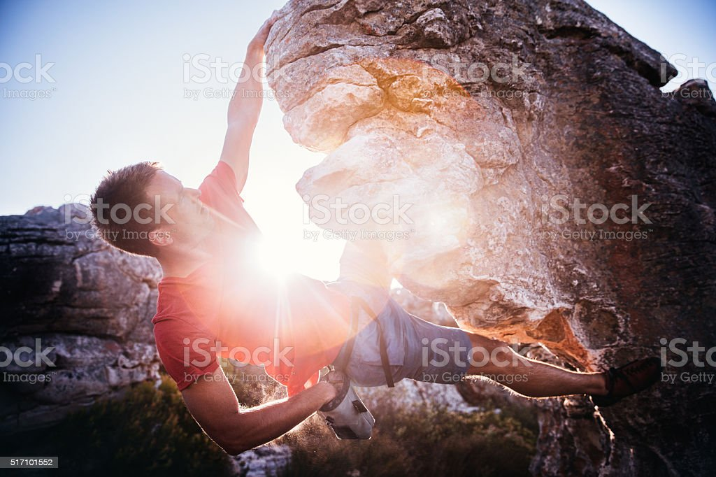 Climber's hand in chalk bag for grip during rock climbing stock photo