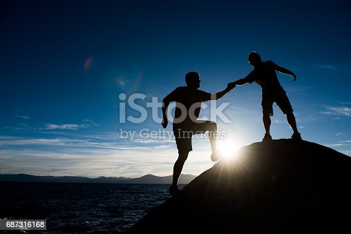 istock climbers helping each other 687316168