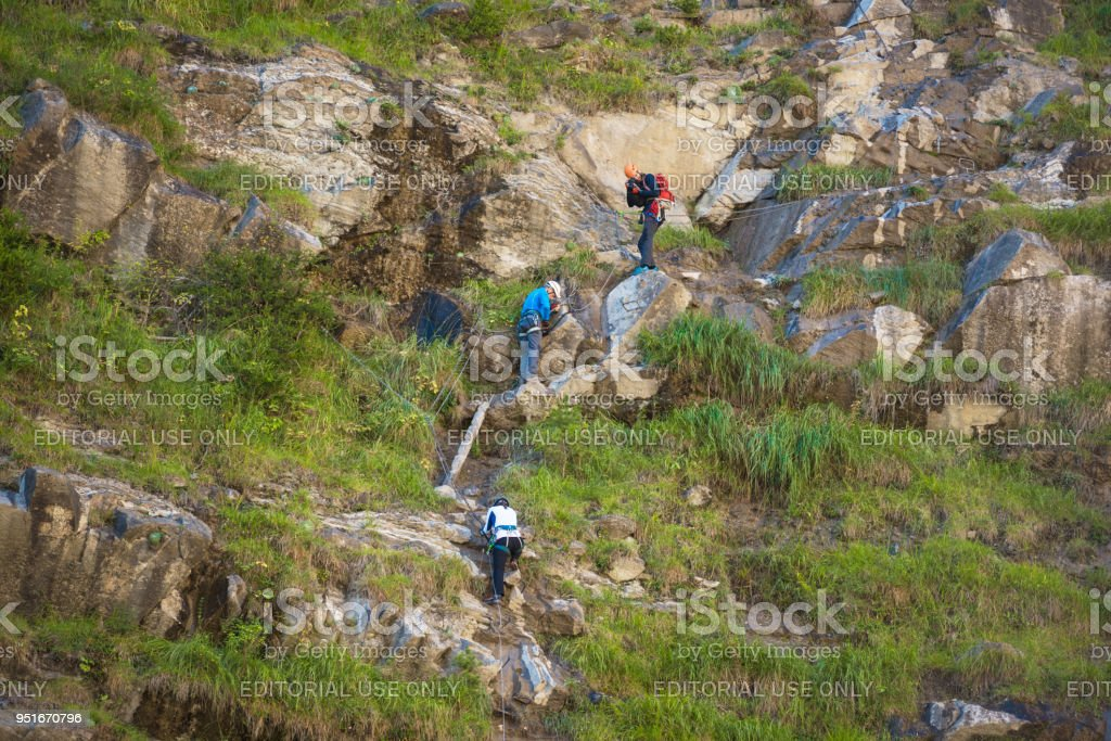 Climbers in via ferrata in Pyrenees, Aragon, Spain. stock photo