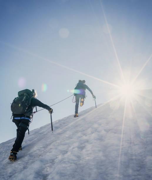 climbers on a snowy slope. - alpinismo foto e immagini stock