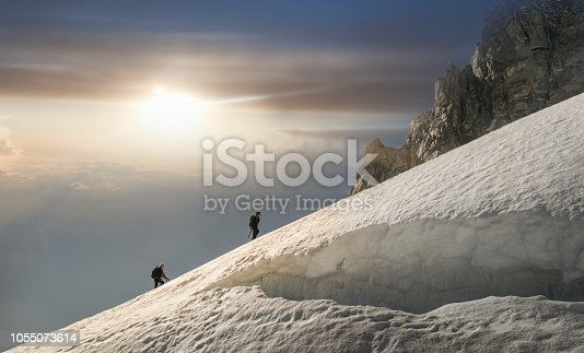 Italy. Courmayeur. Mont Blanc Massif. Climbers on a snowy slope above a huge crevasse in the Mont Blanc Region