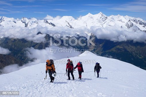 istock Climbers reaching Weissmies mountain's summit 4,017m. - 13,179ft. a Pennine Alps peak in the canton of Valais near the village of Saas-Fee. 687287020