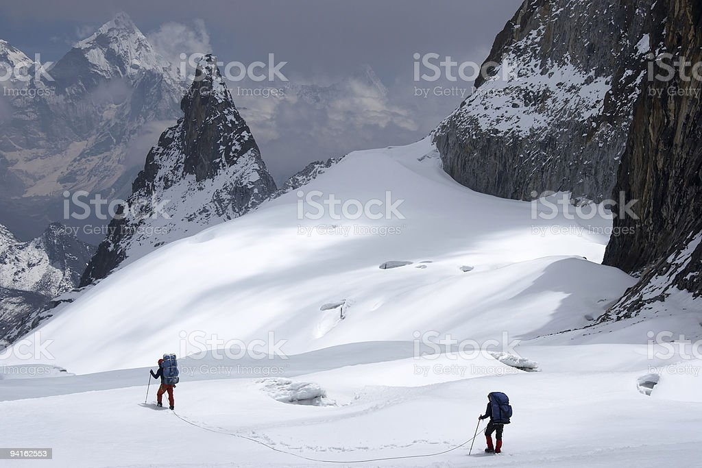 Climbers roped together in search of a way between crevices royalty-free stock photo