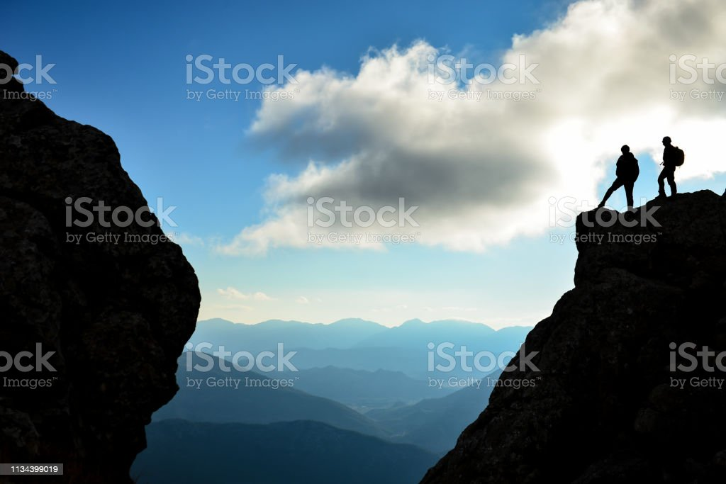 climbers watching the summit from the summit and proud glances stock photo