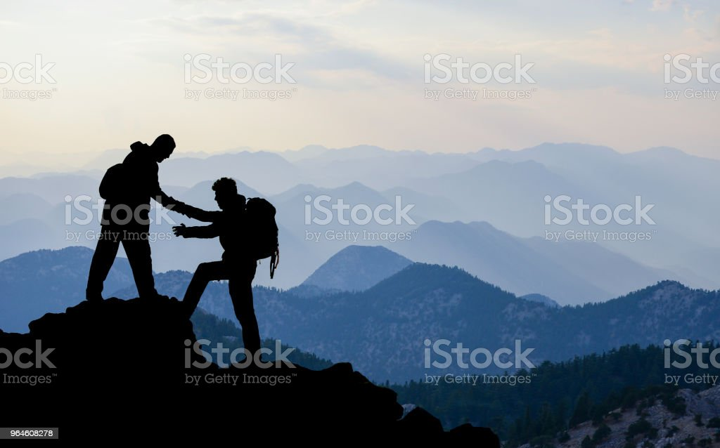 climbers who help in difficult and dangerous rocks stock photo