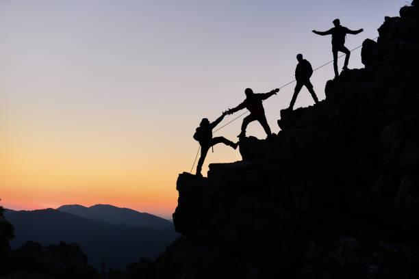 climbers work in harmony and climb - alpinismo foto e immagini stock