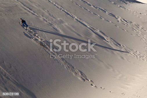 Young boy (11 years old) climbing up the side of a sand dune with late-day shadows.