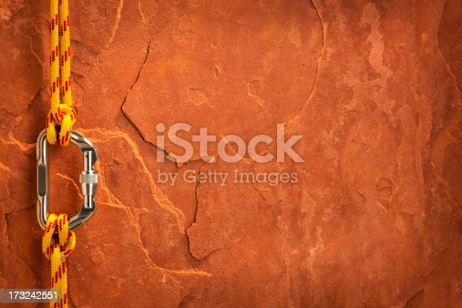 This is a photo taken in the studio of yellow climbing rope attached to a carabiner with a clove hitch knot on each end in front of a sheet of red rock.