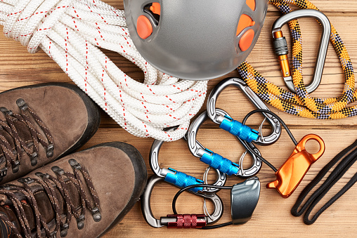 Climbing equipment on wooden background