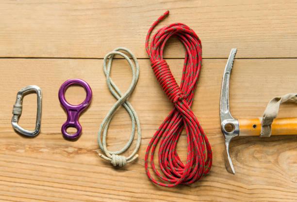 climbing equipment: rope, ice tools, ice ax, eight, carbine on wooden background, top view - isvak bildbanksfoton och bilder