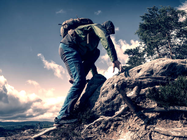 Climbing high up. Mountaineer with backpack hiking stock photo