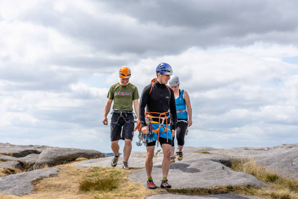 Climbing learners following their climbing instructor in rough terrain stock photo