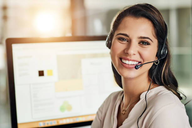 Climbing my way up the customer service ladder Cropped shot of an attractive young businesswoman wearing a headset and sitting alone in her office call centre photos stock pictures, royalty-free photos & images