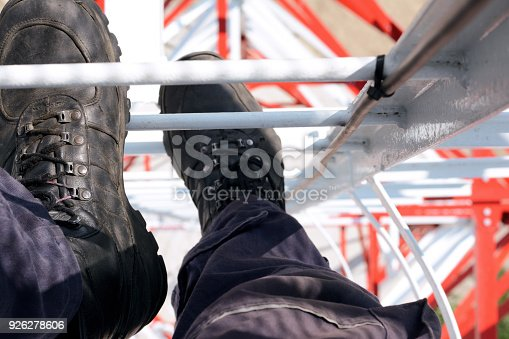 Worker is climbing a high power electric line tower.