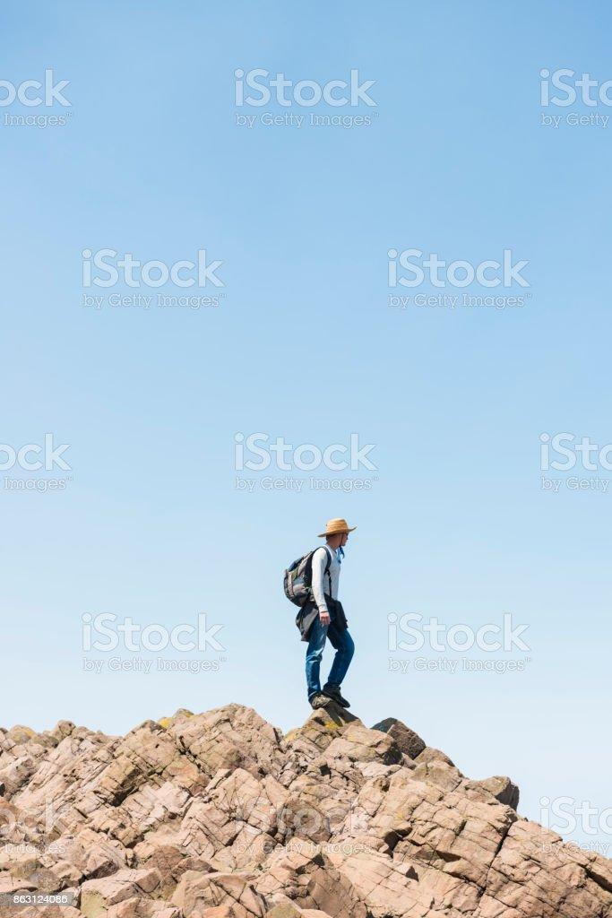 Climbing on rocky reef in Utoro harbor, Hokkaido, Japan stock photo
