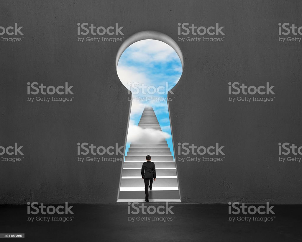 Climbing on stairs with key shape hole and blue sky stock photo