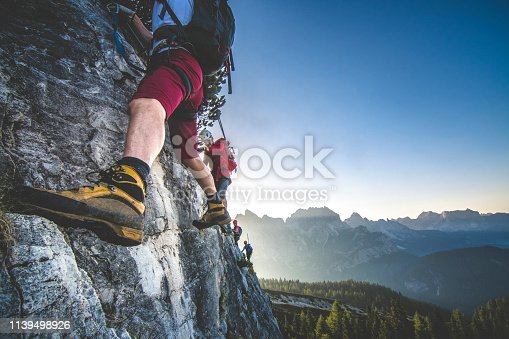 Group of men climbing via ferrata, a secure climbing route found in Alps. Alpine climbing on a sunny day in the mountains.