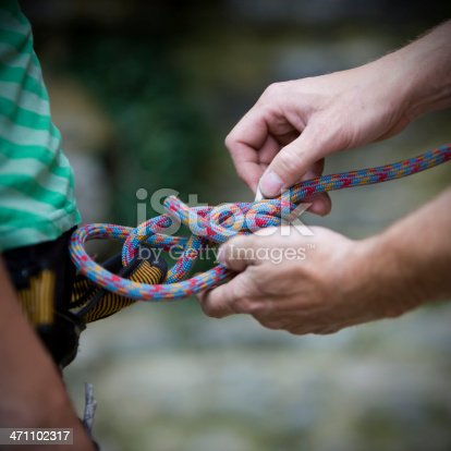 Hands fixing a Knot to belay a female Climber.