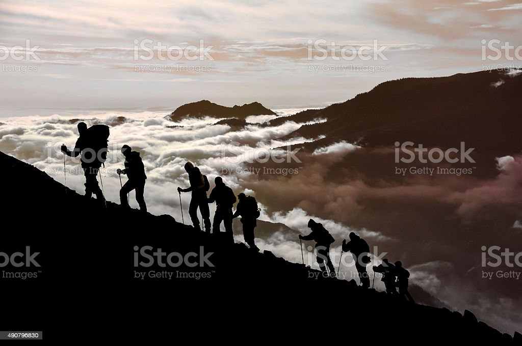 Silhouette of climbing team at dusk