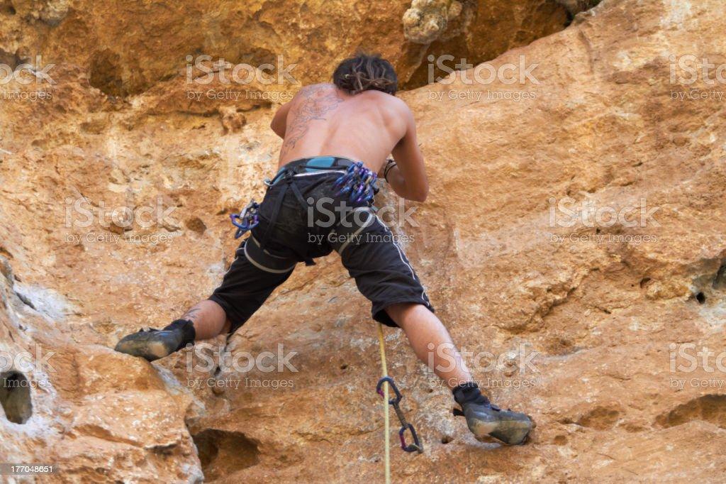 Climbing the rugged rockface royalty-free stock photo