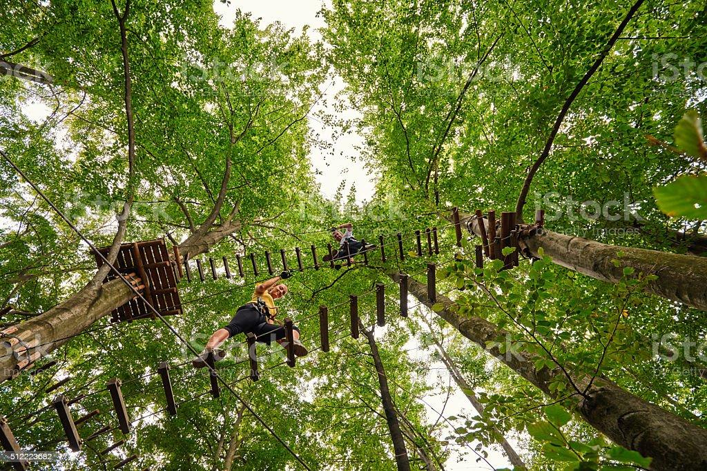 climbing the suspension bridge stock photo