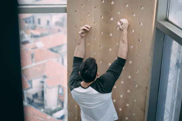 Climbing the wall at the gym with great effort stock photo