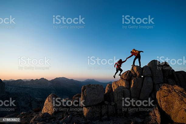 One climber helping the other get to the top of a mountain