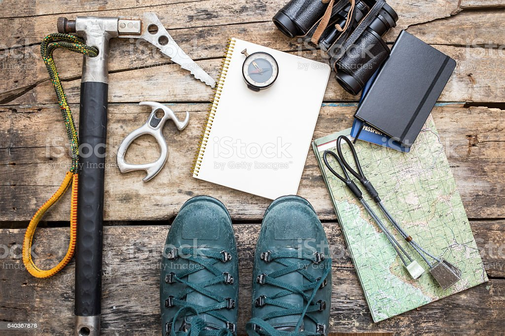 Climbing tools with boots on wood background stock photo