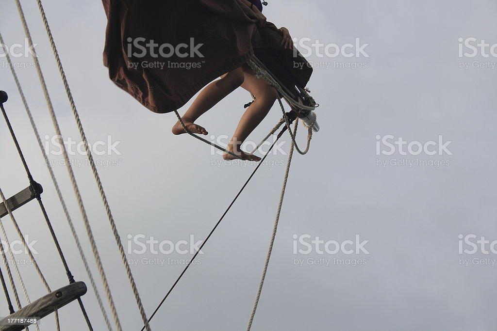 climbing up a mast striking the sails royalty-free stock photo
