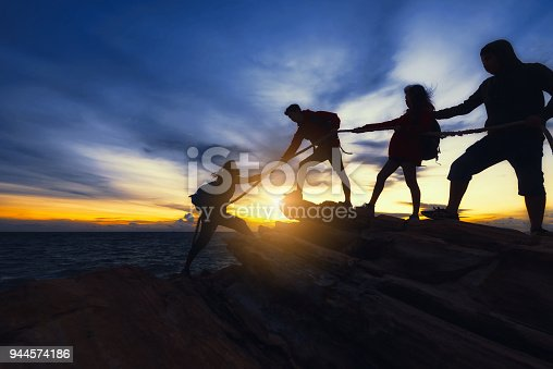 Young asian people climbing up on the mountain,hiking and team work concept.
