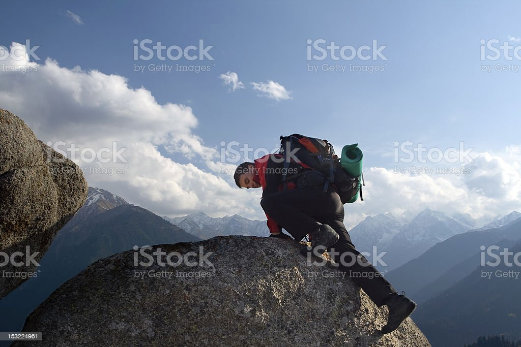 Climbing young adult at the top of summit stock photo
