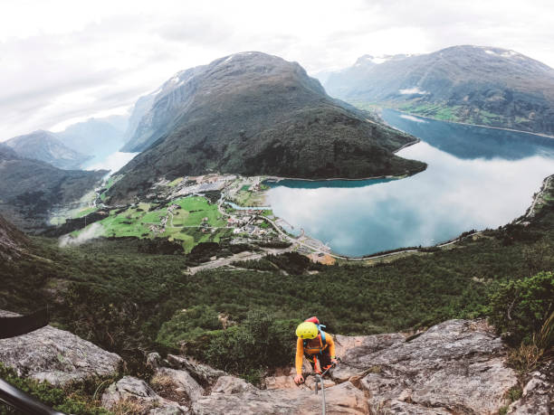 Climer on ferrata trail, enjoying the view of glacier landscape in Norway stock photo