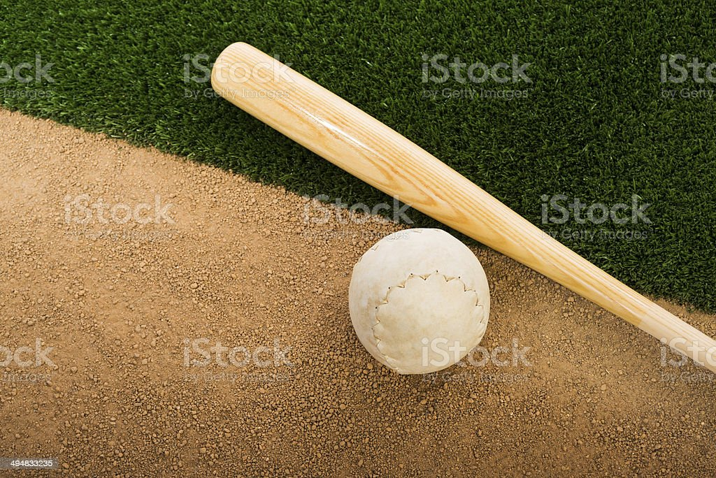Clincher Softball and wooden bat on infield dirt stock photo