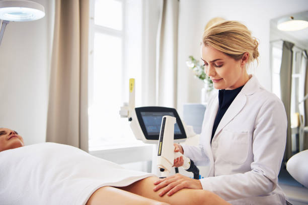 Clinic technician performing laser hair removal on a client's leg stock photo