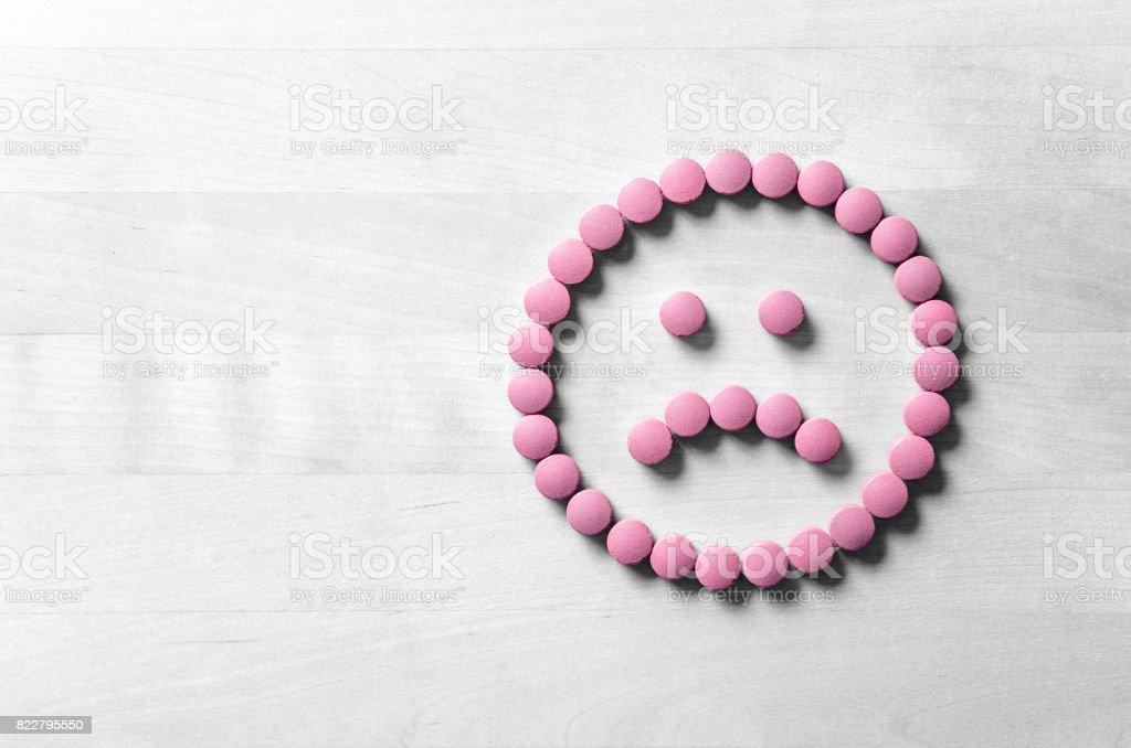 Klinische Depression, psychische Erkrankungen und Störung oder schlechte Gesundheit Dienstleistungskonzept. Traurige Smiley-Gesicht von Pillen, Medizin und Tabletten auf Holztisch gemacht. Das Symbol ist unzufrieden und unglücklich. – Foto