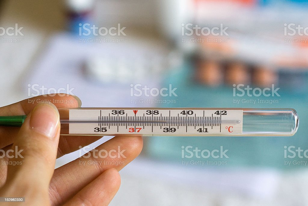 clinical thermometer with high temperature and pills on the background