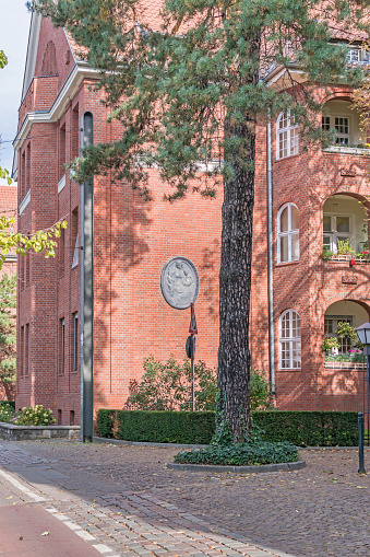 Berlin, Germany - October 3, 2020: Clinker brick building of the Residential estate Paul-Francke-Siedlung built in 1990 with a portrait medallion on the facade (seated woman with two small children)