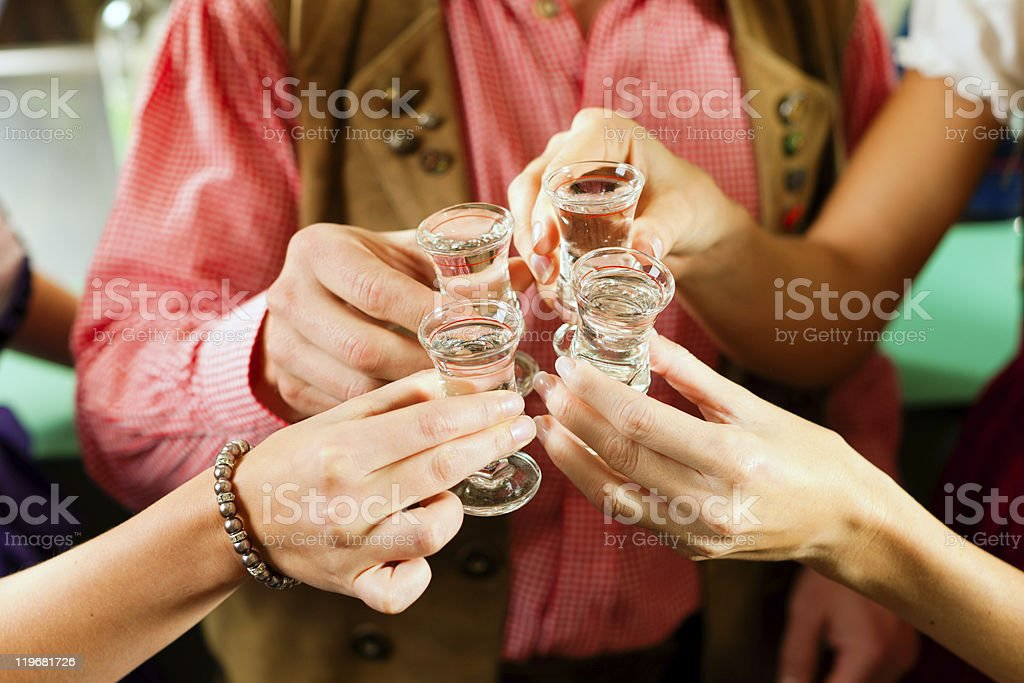 Clinking glasses with hard liquor stock photo