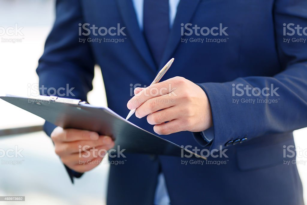 Clipboard and writing pen in usage stock photo