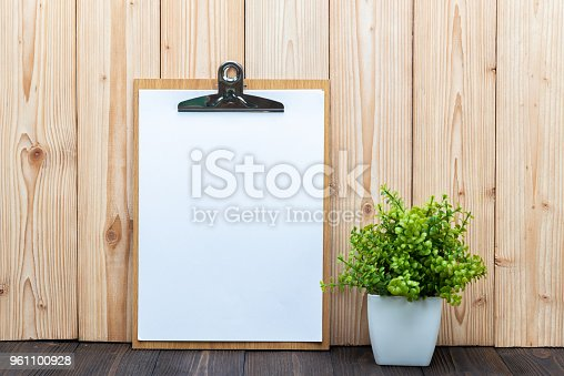 istock Clipboard blank white paper sheet little decoration tree in white vase on wooden background, memo template design 961100928