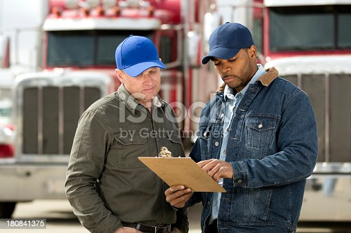 A royalty free image from the trucking industry of two truck drivers having a meeting.