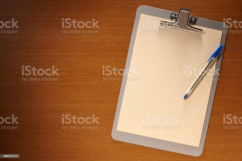 Clipboard with Blank Paper and Pen on a Wooden Background stock photo