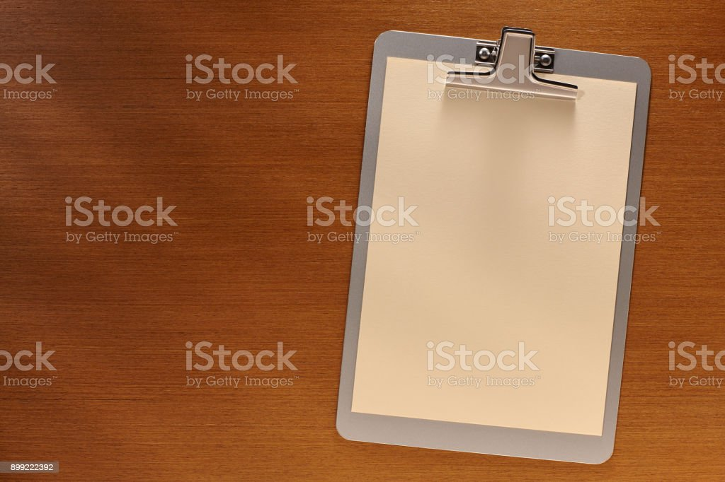 Clipboard with Blank Paper on a Wooden Background stock photo