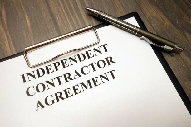 独立した請負業者契約と机の上のペンでクリップボード - 独立 ストックフォトと画像