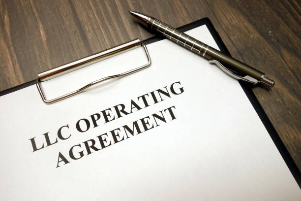 Clipboard with llc operating agreement and pen on desk stock photo
