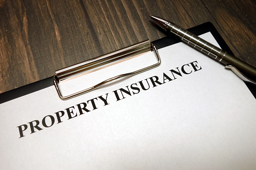 istock Clipboard with property insurance mockup and pen on desk 1149897427