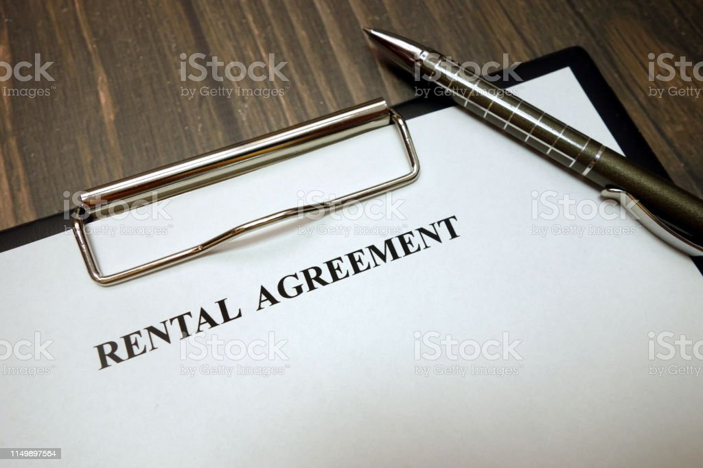 Clipboard with rental agreement and pen on wooden desk background