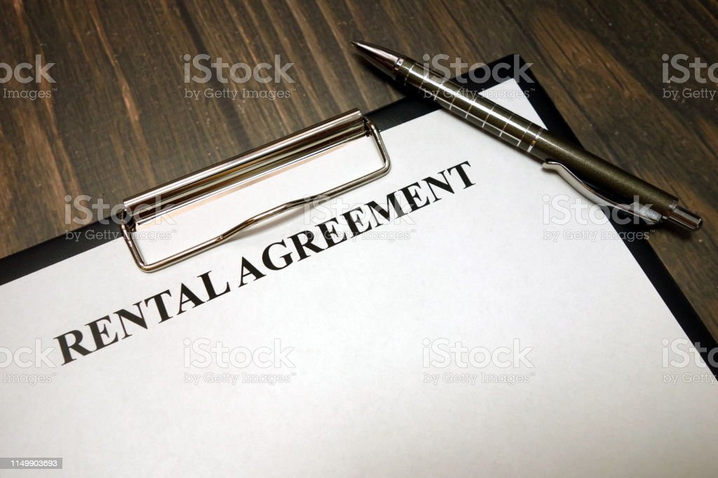 Clipboard with rental agreement mockup and pen on wooden desk...