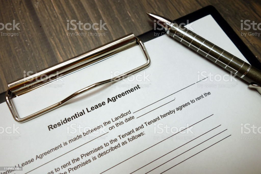 Clipboard with residential lease agreement and pen on wooden desk...