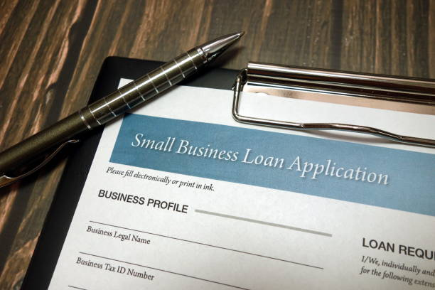 Clipboard with small business loan application form and pen on desk stock photo